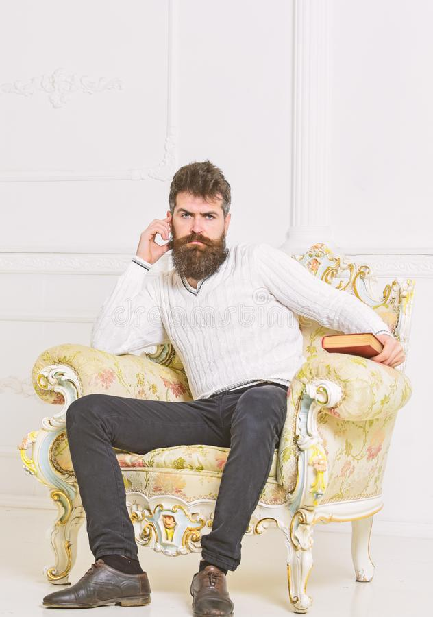 Reflections on literature concept. Connoisseur on thoughtful face finished reading book. Man with beard and mustache. Sits on armchair, holds book, white wall stock image