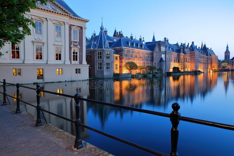 Reflections of the Mauritshuis and the Binnenhof 13 century gothic castle on the Hofvijver lake at dusk during the blue hour royalty free stock photography