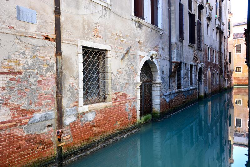 Reflections on a narrow water canal in Venice in the San Marco district. One of the most beautiful carnivals in the world in the city, Venice, the most beautiful royalty free stock photography