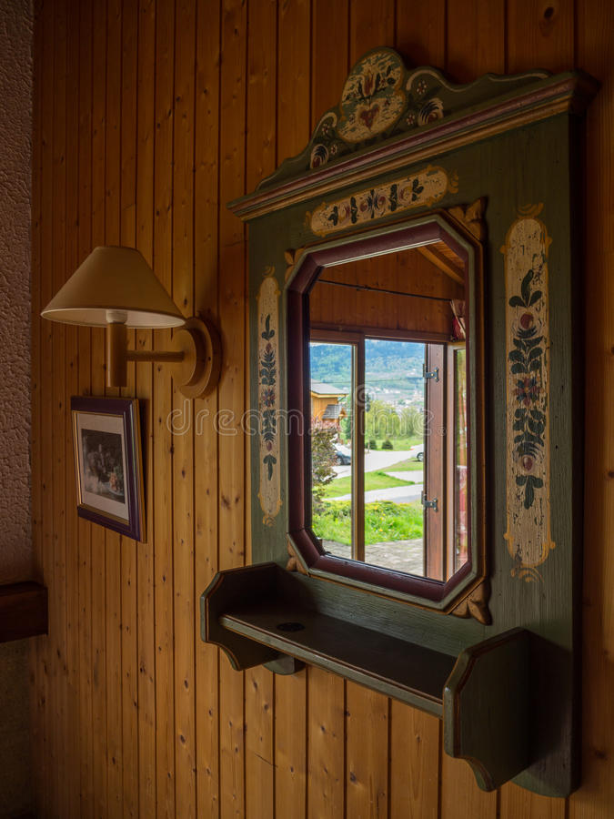 Reflections of outside in a classic antique mirror. Inside a wooden chalet royalty free stock image