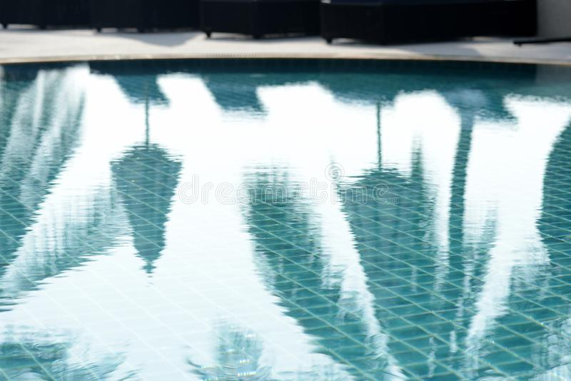 Reflections of palm trees and beach umbrellas in the pool in the morning. Blurred background royalty free stock photography