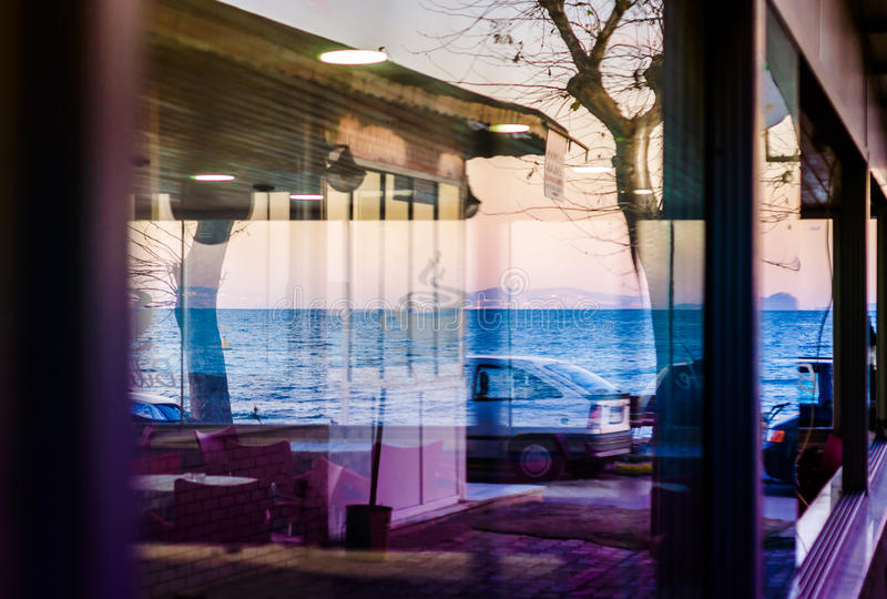 Reflections On Restaurant Window. Reflections of a street next to the shoreline in the glass windows of a local restaurant in Cinarcik town of Turkey. Cinarcik royalty free stock photography
