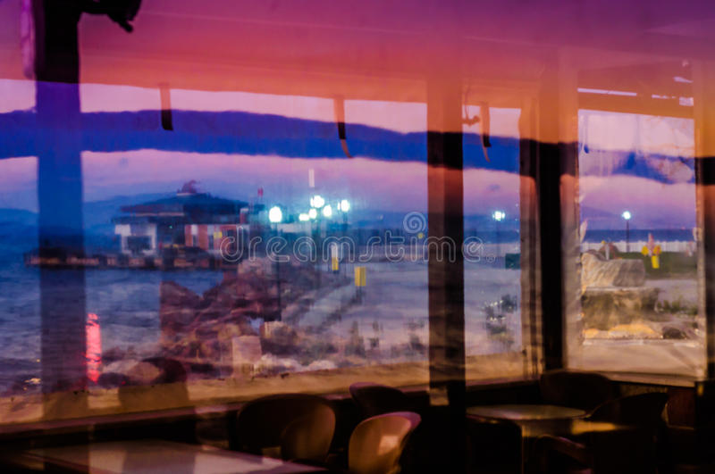 Reflections On Restaurant Window. Reflections of a street next to the shoreline in the glass windows of a local restaurant in Cinarcik town of Turkey. Cinarcik royalty free stock images