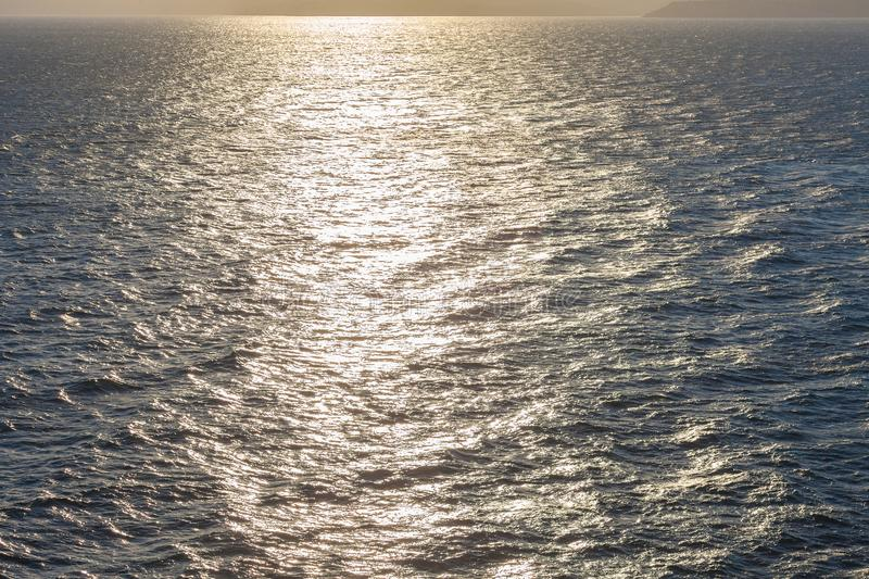Reflections of the setting sun over the waves of the sea royalty free stock photography