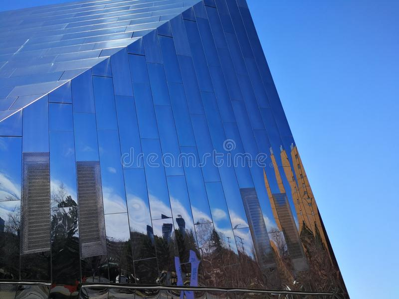 Reflections on side of modern glass structure against blue sky stock photography