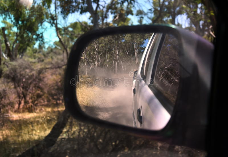 Reflections in a side view mirror of a car driving in the bush. Rear view car mirror in forest live green. Dirt road leading up to a slavery plantation royalty free stock photos