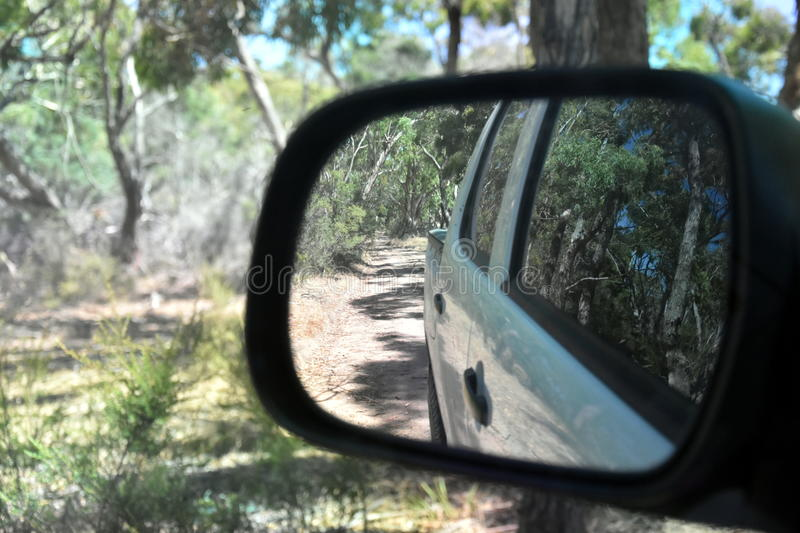 Reflections in a side view mirror of a car driving in the bush. Rear view car mirror in forest live green. Dirt road leading up to a slavery plantation stock image