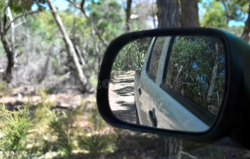 Reflections in a side view mirror of a car driving in the bush. Rear view car mirror in forest live green. Dirt road leading up to a slavery plantation royalty free stock photo