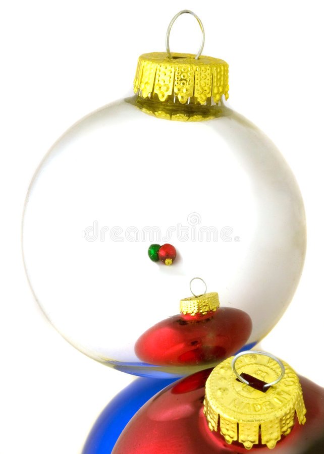 Reflections in silver ornament. Classic red, blue and green reflective glass ornaments reflecting in silver ornament isolated on white background stock photo