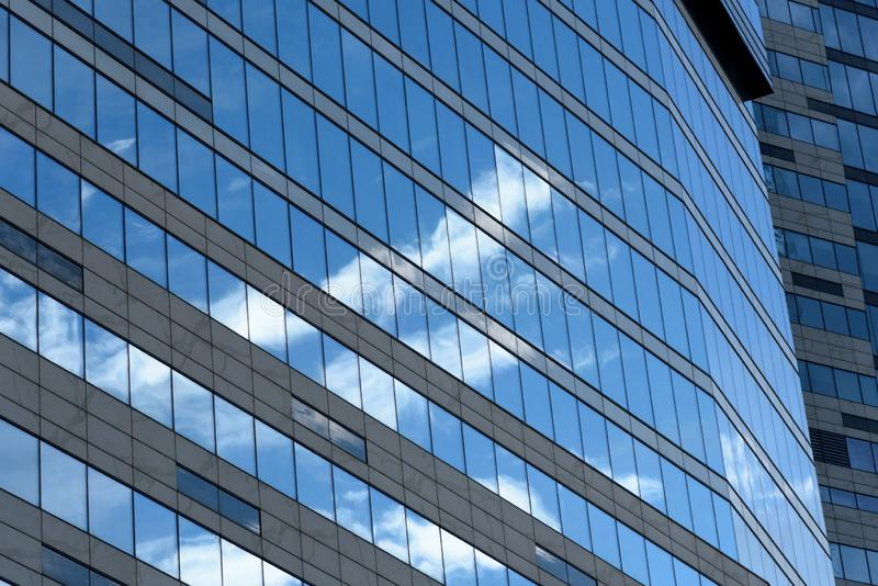 Reflections of sky and clouds in the windows of a modern business building. Low angle view. Business District Moscow City. Close- royalty free stock photo