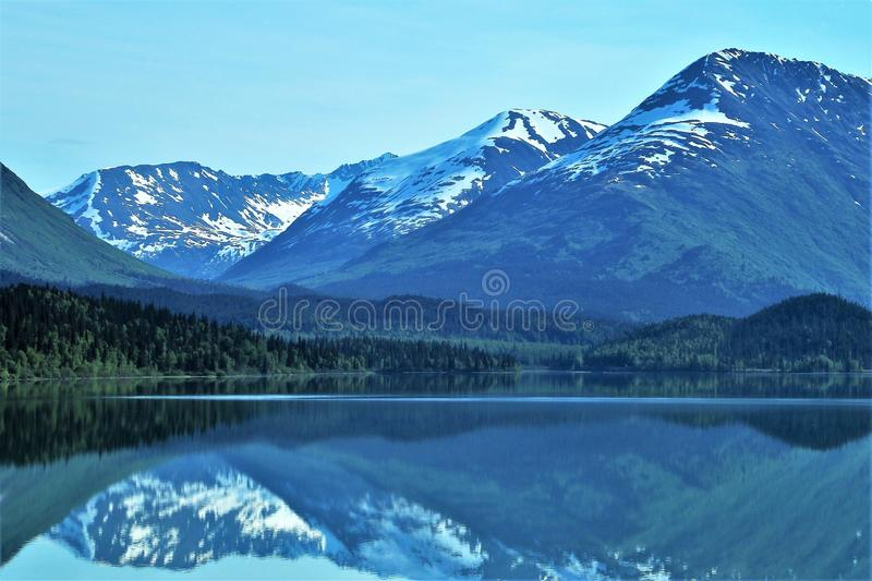 Reflections of Alaskan mountains in lake stock photography