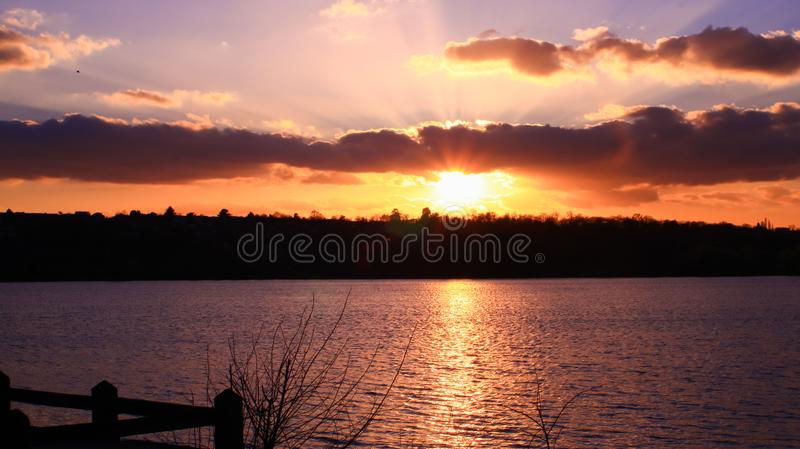 Reflections of the sun on the lake with vegetation in the foreground. Rays of the sun crossing clouds in a beautiful landscape in the countryside royalty free stock photo