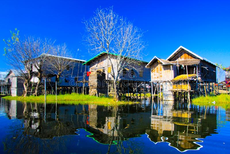 Reflections of traditional stilts wood houses in smooth as glass water contrasting with cloudless blue sky. Inle Lake, Myanmar royalty free stock image