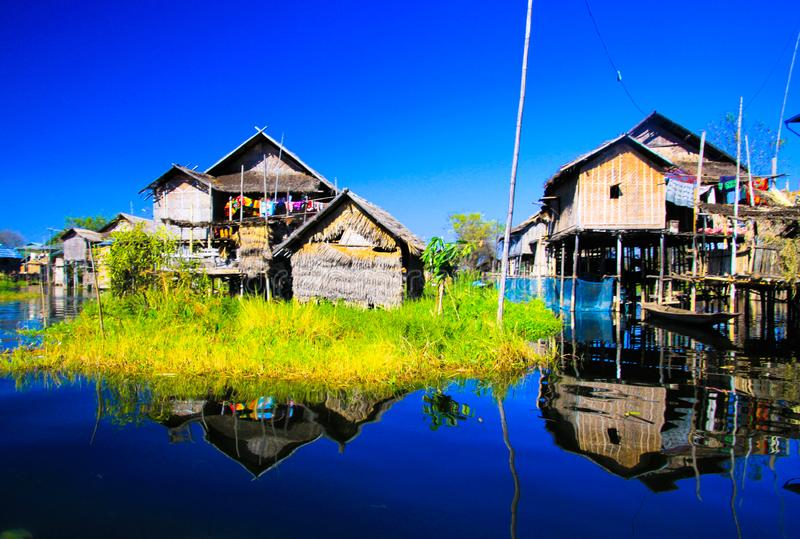 Reflections of traditional stilts wood houses in smooth as glass water contrasting with cloudless blue sky. Inle Lake, Myanmar royalty free stock photos