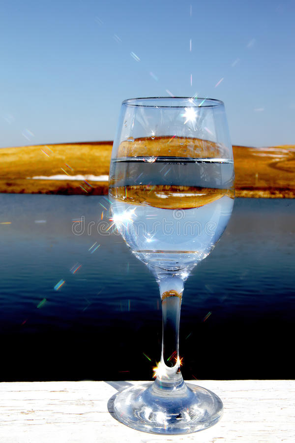 Reflections in water. In a glass with the sun behind stock images