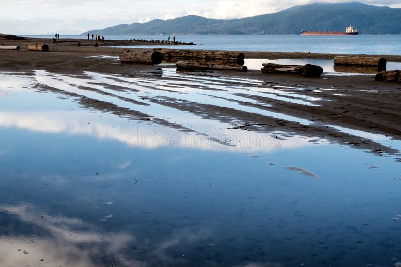 Reflections in waters and distant views of mountains are visible in the Spanish Banks coastline of the city of Vancouver. Blue waters and reflections create royalty free stock image