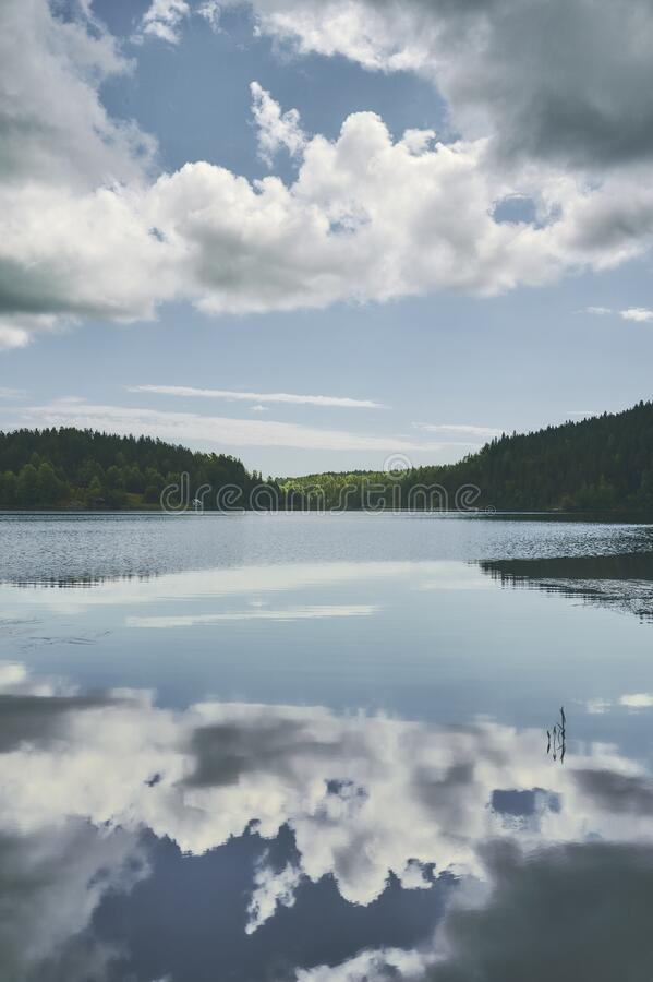 Reflections of white clouds in still blue water. Mountain lake royalty free stock image