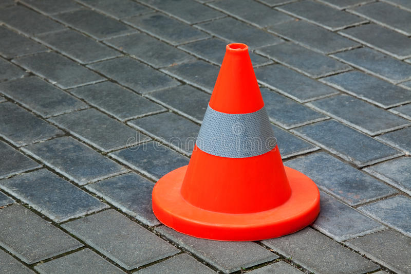 Reflective cone on a road. Bright reflective cone on a grey tile road royalty free stock image