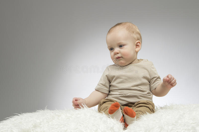 Reflective cute boy sitting on the white blanket, studio shot, isolated on grey background, funny baby portrait.  royalty free stock image