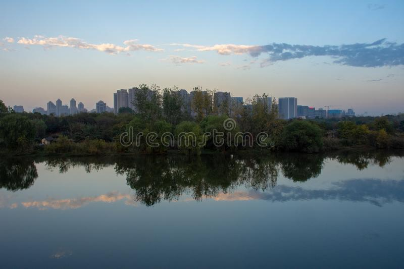A reflective evening shot of trees and buildings. In Wuhan, China on an unusually low pollution day royalty free stock images
