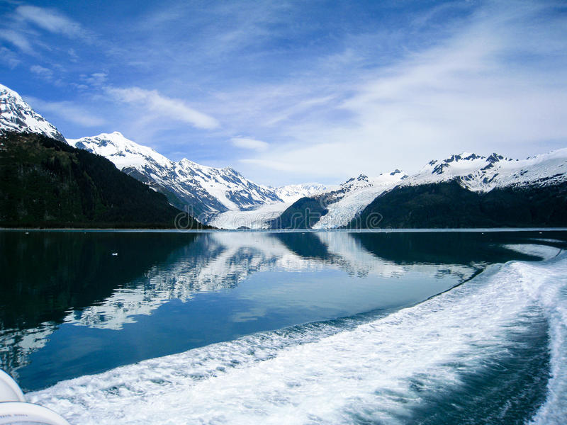 Reflective glaciers of Prince William Sound in Alaska. The scenery of glaciers flow down from the mountains into the water next to the rocky cliffs of Prince stock photos