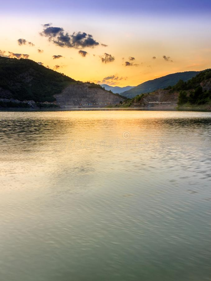 Golden, reflective lake vertical shot during sunset with dramatic sky. Reflective lake vertical shot during sunset with dramatic sky, silky water and space for royalty free stock photo