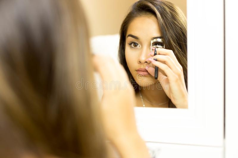 Reflective on mirror mixed race woman making curl eyelashes usin stock photography