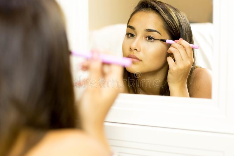 Mixed race young woman with brush eye liner on looking in the mi. Reflective mixed race young woman with brush eye liner on with looking in the mirror stock images