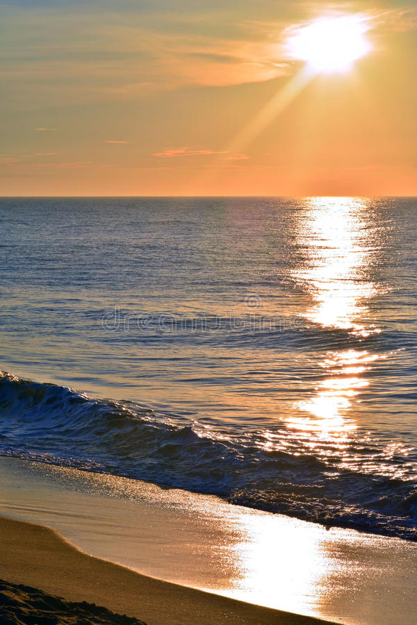 Reflective Seas Beneath A Golden Sunrise. The seas look reflective beneath a golden summer sunrise at the seashore royalty free stock image
