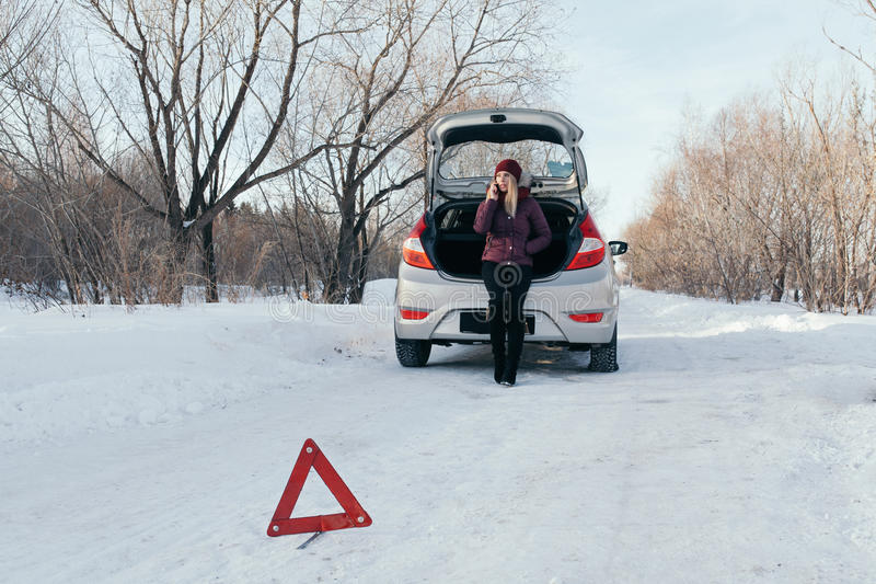 Reflective warning triangle before vehicle, an emergency situation on the road in winter, calls for help, woman talking royalty free stock photo