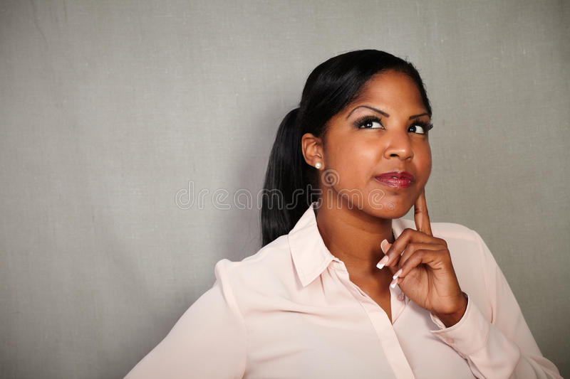 Reflective woman contemplating with hand on chin stock photos