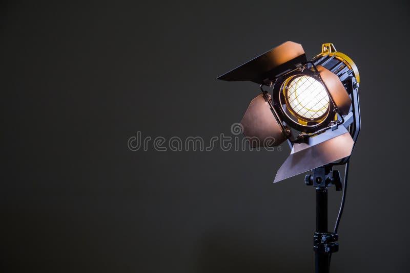 Reflector con la lámpara del halógeno y la lente de Fresnel en un fondo gris Equipo de iluminación para tirar imagenes de archivo