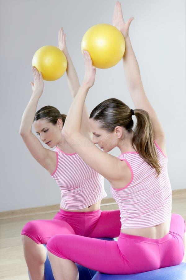 Refleje la gimnasia del deporte de la bola de la estabilidad de la mujer de la gimnasia de los pilates foto de archivo