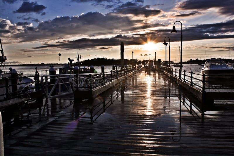 Reflejo ligero de la puesta del sol en el embarcadero mojado de la pesca foto de archivo libre de regalías