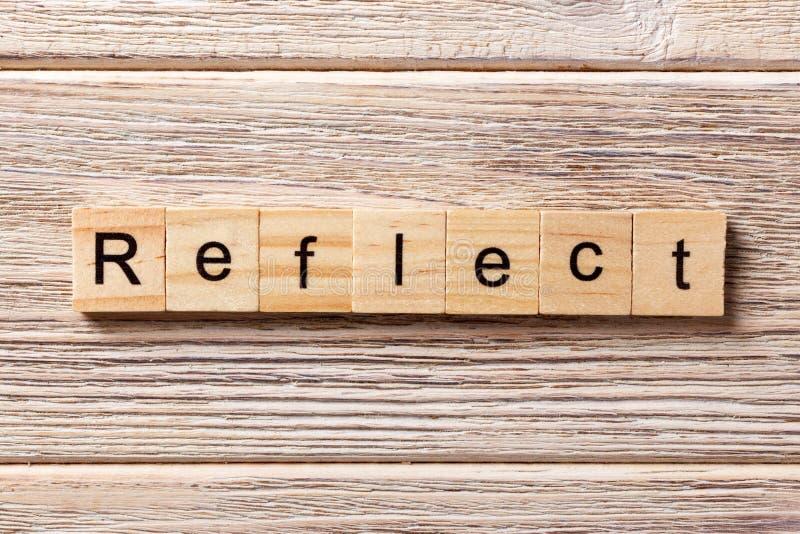 Reflektera ordet som är skriftligt på träsnittet Reflektera text på tabellen, begrepp arkivbild