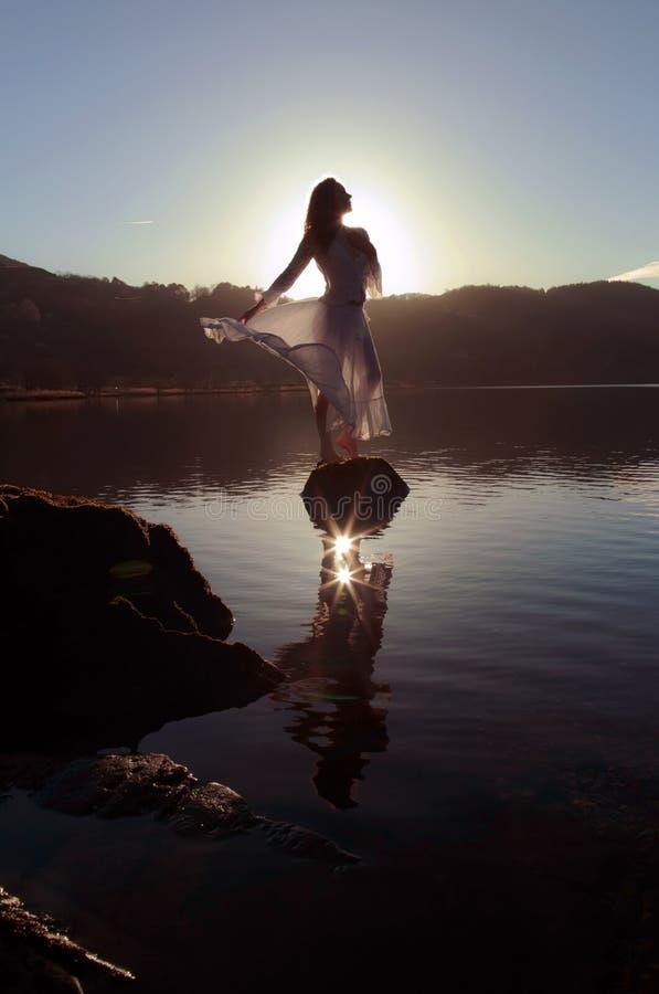 Reflekterade iklädd vit för den härliga flickan, silhouetted av solen i den stilla sjön arkivfoto