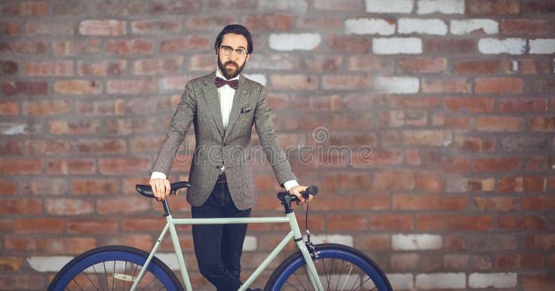 Reflekterande hipsterman med en cykel som är främst av den röda stenväggen royaltyfri fotografi