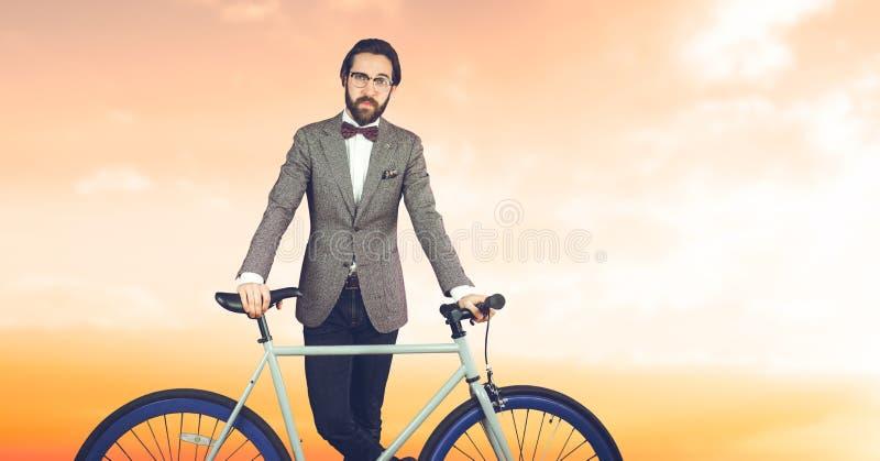 Reflekterande hipsterman med en cykel som är främst av orange bakgrund royaltyfri bild