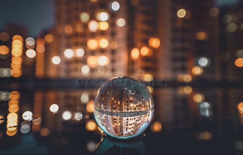 Reflekterande nattcityscape för kristallkula arkivbilder