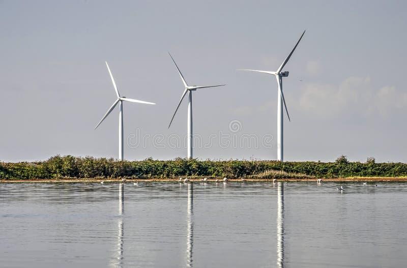 Reflektieren mit drei Windmühlen lizenzfreies stockbild