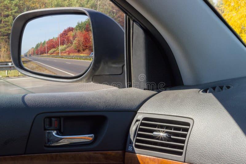Reflektierte Landstraße im Autoseitenrückspiegel im Herbst stockfoto