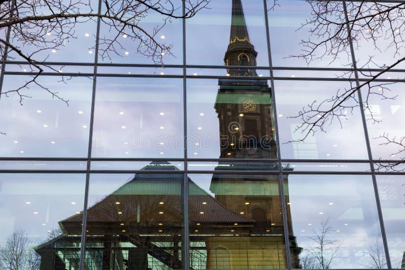Reflektion av den gamla kristna kyrkan i den moderna businens glasvägg royaltyfri fotografi