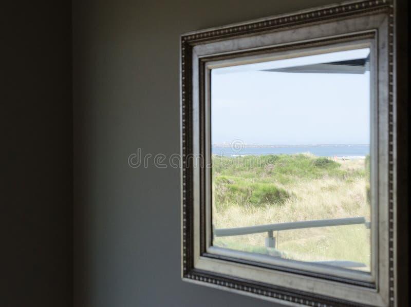 Reflektion av dyner och bögar i en spegel i metallstommen inuti lägenheten royaltyfria bilder