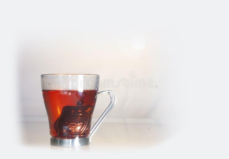 Reflektion av glasbägare på glasbordet som visar en kopp med varmt vatten och en enda silverteapot när teet bereds arkivbilder