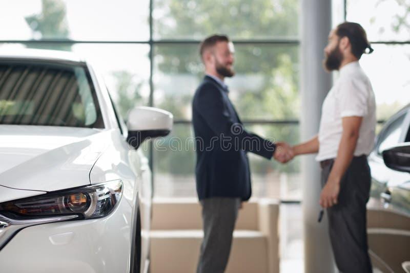 Reflektor biały samochód i mężczyźni trząść ręki za obrazy stock