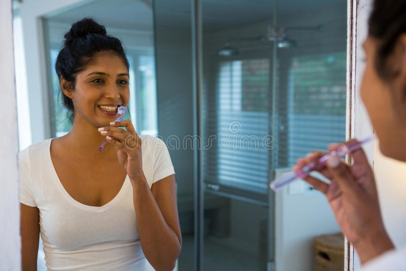 Refletir de escovadela da mulher no espelho foto de stock royalty free