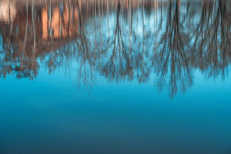 Reflexão abstrata das silhuetas na água Casa e ?rvores Fundo art?stico da natureza foto de stock