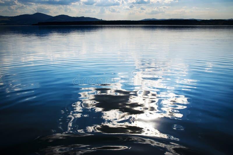 Reflexão abstrata de uma nuvem em uma superfície da água do lago imagem de stock