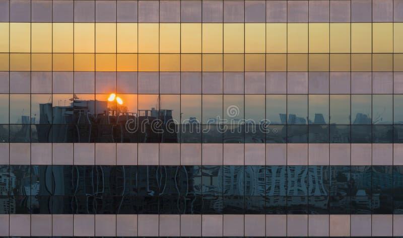 Reflexão da cena crepuscular da arquitetura da cidade do por do sol em Windows de Skys fotos de stock royalty free