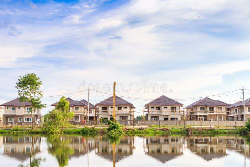 Reflexão da construção de casa nova com água no lago no canteiro de obras residencial da propriedade fotos de stock royalty free